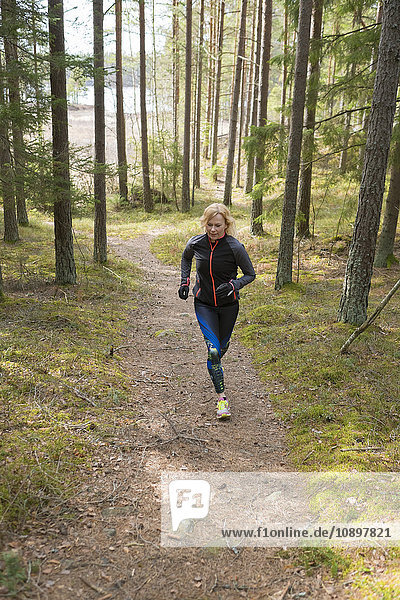 Schweden  Ostergotland  Lotorp  Frau läuft durch den Wald
