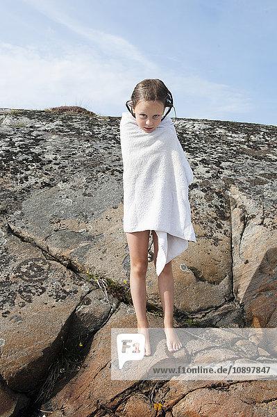 Schweden  Halland  Onsala  Mädchen (6-7) in Handtuch gewickelt  auf Felsen stehend