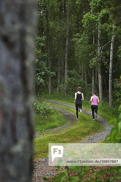 Schweden  Ostergotland  Vikbolandet  Zwei Frauen beim Laufen im Wald