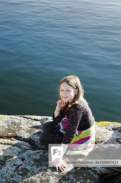 Schweden  Bohuslan  Smogen  Porträt eines Mädchens (8-9) am Felsstrand sitzend