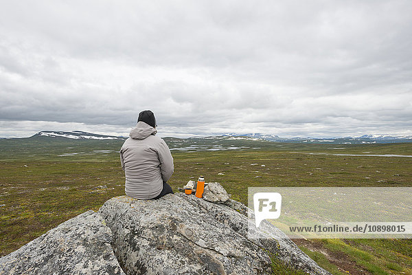Schweden  Harjedalen  Flatruet  Frau mit isoliertem Getränkebehälter auf Felsen sitzend und auf Berge blickend
