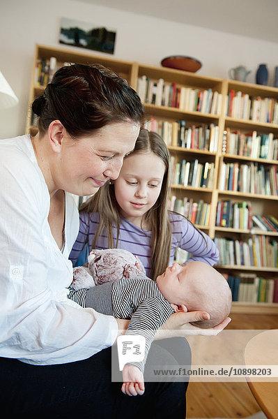 Schweden  Mädchen (10-11) beobachtende Mutter mit Bruder (0-1 Monate) in den Armen