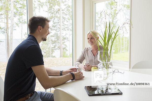 Schweden  Mann und Frau sitzen und trinken zu Hause