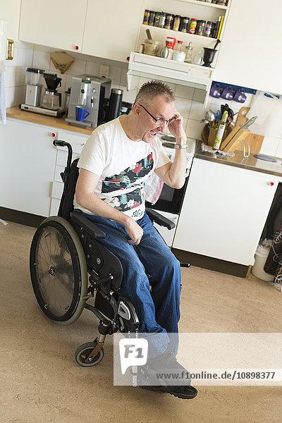 Schweden  Mann im Rollstuhl in der Küche