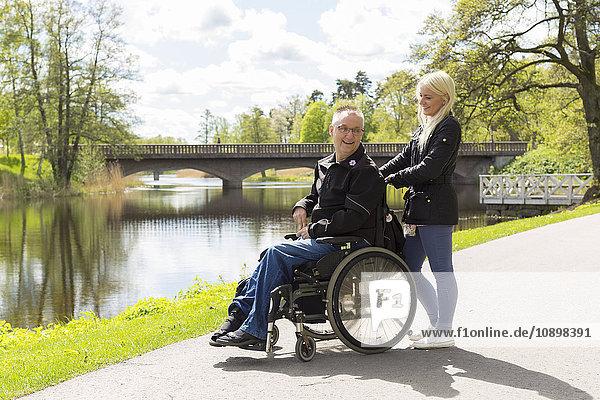 Schweden  Ostergotland  Mjolby  Mann im Rollstuhl mit persönlicher Assistentin im Park