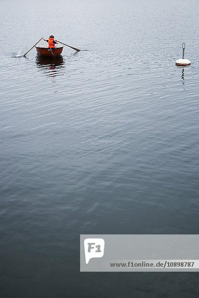 Schweden  Uppland  Runmaro  Barrskar  Junge (6-7) im Ruderboot
