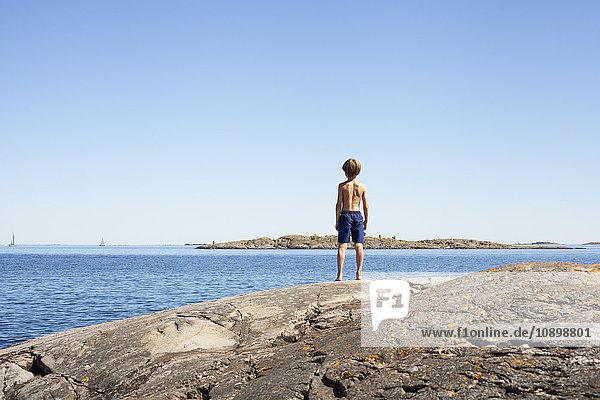 Schweden  Uppland  Runmaro  Barrskar  Rückansicht des Jungen (6-7) beim Blick aufs Meer