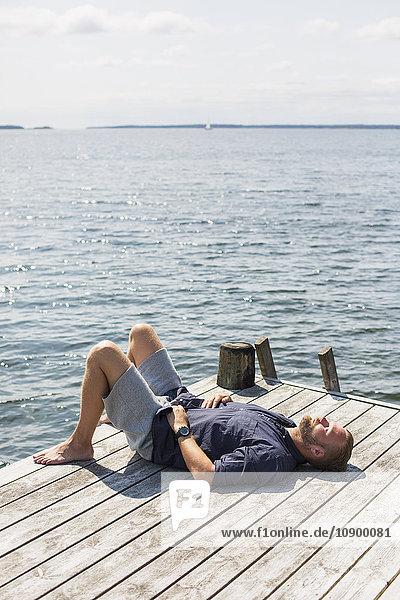 Sweden  Stockholm Archipelago  Grasko  Man sunbathing on jetty