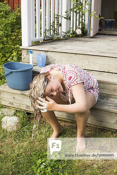 Sweden  Stockholm Archipelago  Grasko  Girl (12-13) washing hair outside