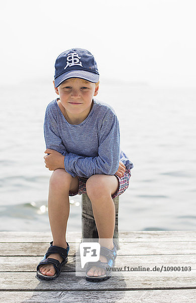 Sweden  Stockholm Archipelago  Grasko  Boy (6-7) sitting on pole on jetty