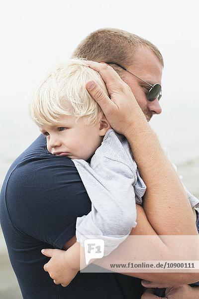 Sweden  Gotland  Ljugarn  Man embracing boy (2-3)