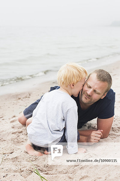 Sweden  Gotland  Ljugarn  Boy (4-5) kissing man on chick