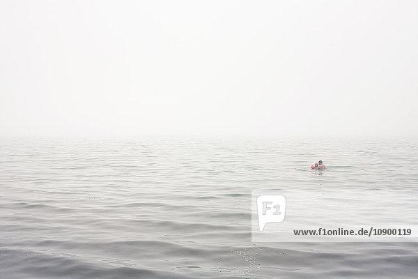 Sweden  Gotland  Ljugarn  Man and boy (4-5) swimming in foggy sea