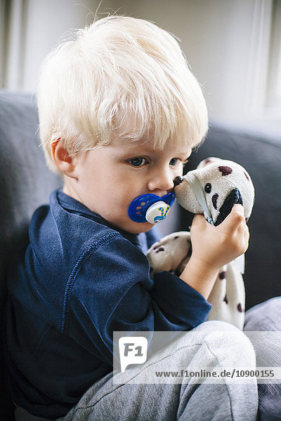 Sweden  Boy (4-5) with pacifier and toy