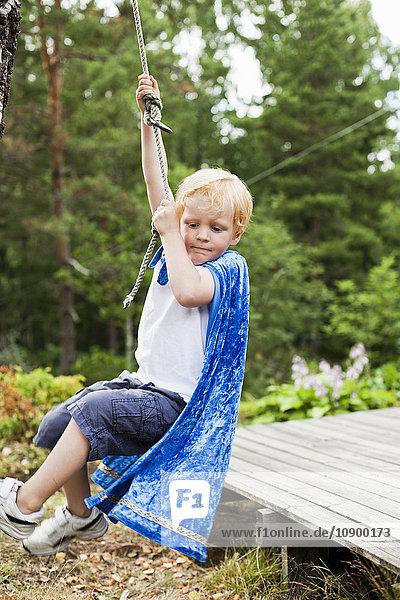 Sweden  Sodermanland  Stockholm Archipelago  Musko  Boy (4-5) swinging on rope