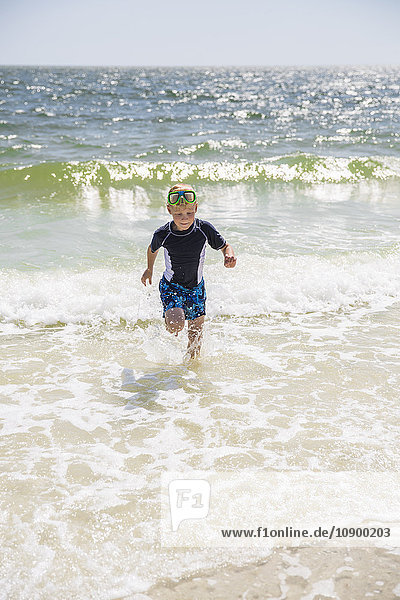 USA  Florida  Little boy (6-7) with scuba mask running against sea