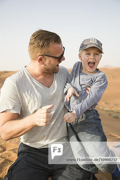 United Arab Emirates  Dubai  Father with son (6-7) in desert