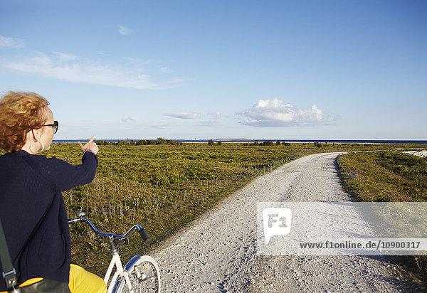 Schweden  Gotland  Furillen  Frau auf dem Fahrrad zeigend