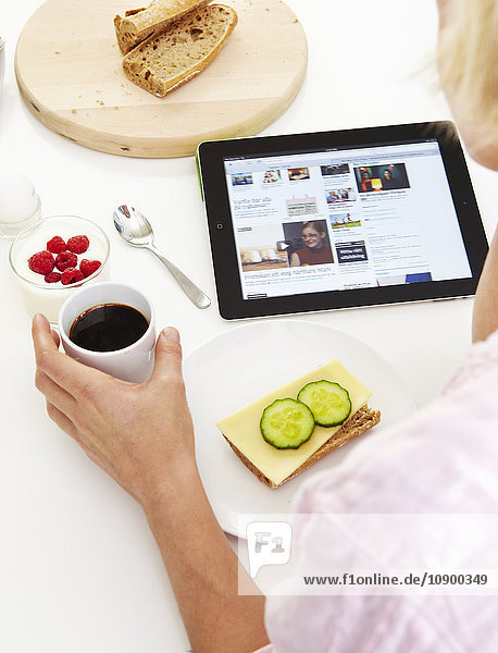 Frau  die beim Frühstück digitale Tabletten benutzt