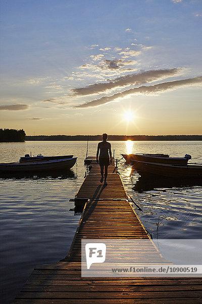 Schweden  Vastra Gotaland  Skagern  Frau  die bei Sonnenuntergang auf dem Pier im See spazieren geht