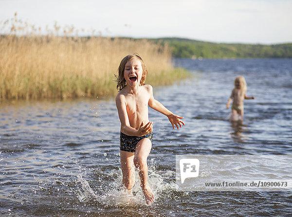 Sweden  Vastergotland  Lerum  Lake Aspen  Boy (8-9) and girl (6-7) playing in lake