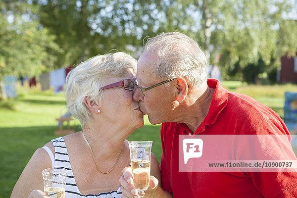 Schweden  Seniorenpaar-Toasting mit Sektflöte und Küssen