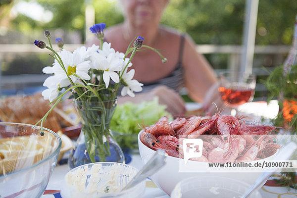 Schweden  Vastergotland  Lerum  Schale mit Garnelen und Blumenvase auf Tisch  Frau sitzend im Hintergrund