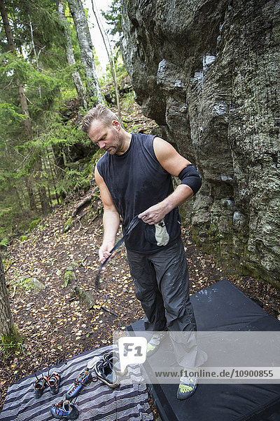 Sweden  Sodermanland  Tyreso  Sportsman with rock climbing equipment in forest
