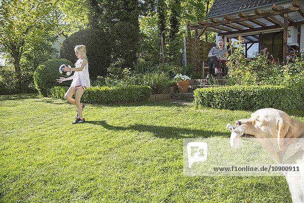 Deutschland  Niedersachsen  Mädchen (10-11) beim Spielen vor dem Haus  Mann im Hintergrund