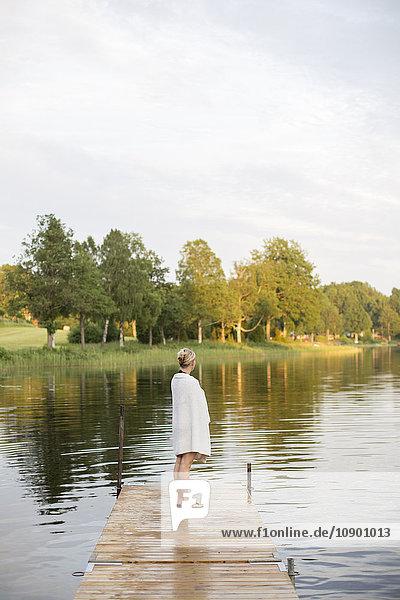 Schweden  Smaland  Braarpasjon  Reife Frau in Handtuch gewickelt am Steg stehend