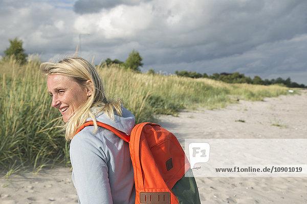 Schweden  Skane  Soderslatt  Beddinge  Smiley Frau mit Rucksack unter bewölktem Himmel