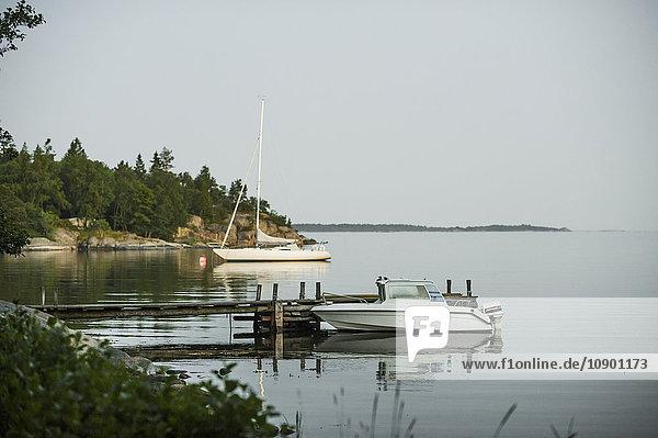 Schweden  Uppland  Stockholms Skargard  Graddo  Motorbaot und Segelboot liegen am Seeufer.