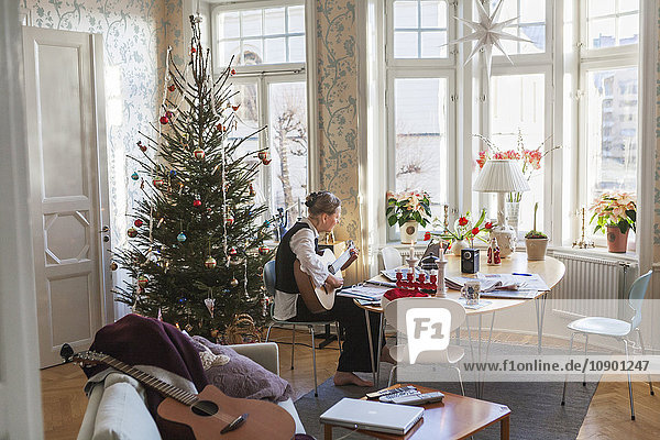 Sweden  Senior woman playing guitar in living room