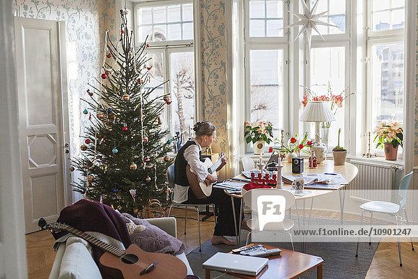 Schweden  Seniorin beim Gitarrespielen im Wohnzimmer