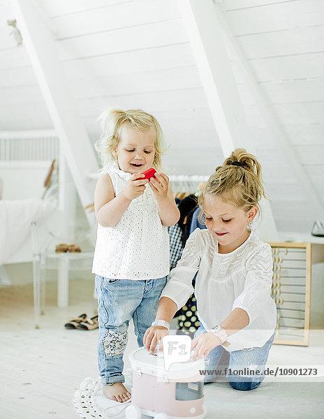 Schweden  Schwestern (2-3  6-7) beim Spielen mit Spielzeugwagen im Schlafzimmer
