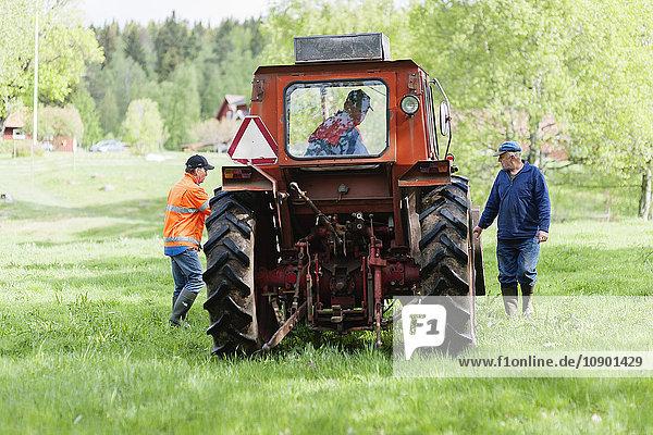 Schweden  Vastmanland  Bergslagen  Hallefors  Landwirt mit Traktor im Feld