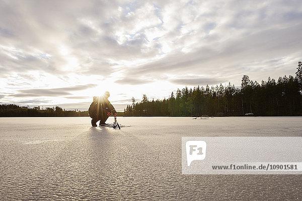 Schweden  Vastmanland  Bergslagen  Hallefors  Natsjon  Mann  der sich auf das Eisangeln auf dem zugefrorenen See vorbereitet.