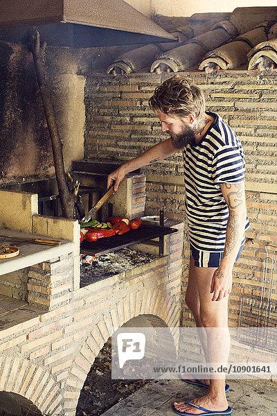 Italien  Latium  Mann beim Grillen