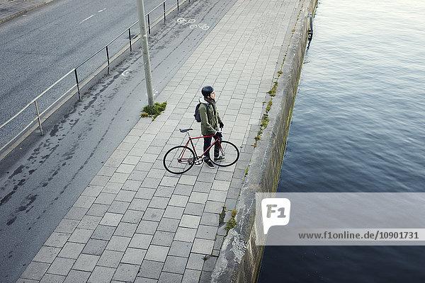 Schweden  Sodermanland  Stockholm  Sodermalm  Slussen  Mittlerer Erwachsener Mann mit Fahrrad am Ufer des Flusses.