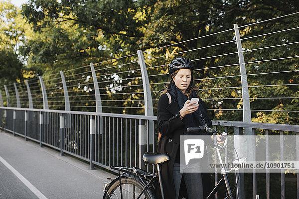 Schweden  Sodermanland  Stockholm  Vasterbron  Junge Frau auf dem Fahrrad mit dem Telefon