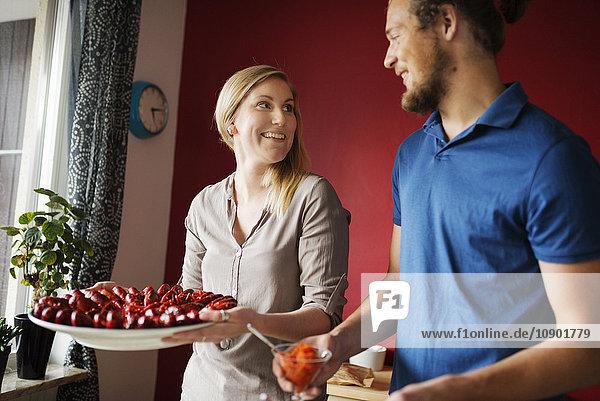 Schweden  Mann und Frau halten Krebse auf Teller