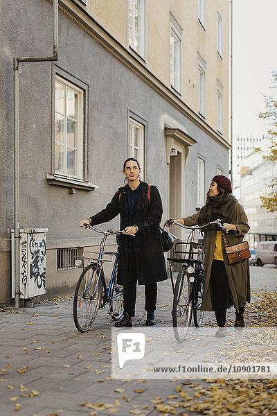 Schweden  Uppland  Stockholm  Vasastan  Zwei Personen zu Fuß mit dem Fahrrad