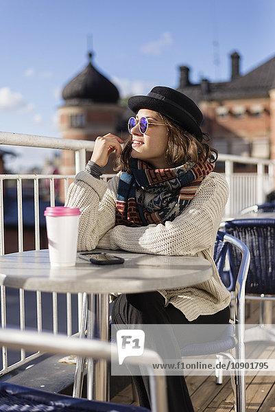 Schweden  Vasterbotten  Umea  Junge Frau sitzend im Straßencafé