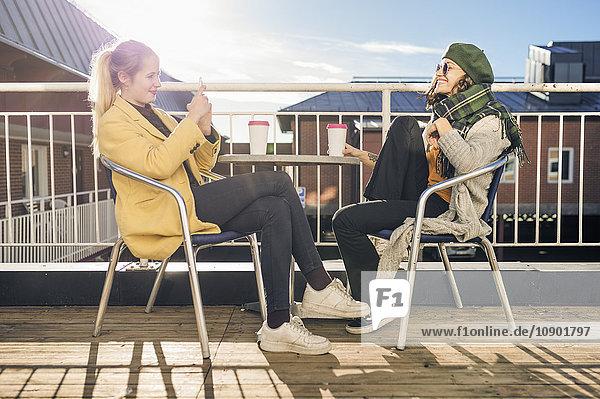 Schweden  Vasterbotten  Umea  Zwei junge Frauen  die im Freien sitzen