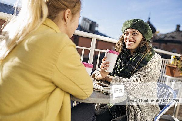 Schweden  Vasterbotten  Umea  Zwei junge Frauen sitzen im Freien mit Kaffee