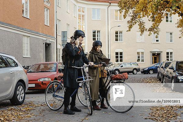 Schweden  Uppland  Stockholm  Vasastan  Rodabergsbrinken  Zwei Personen stehen mit Fahrrädern im Freien.