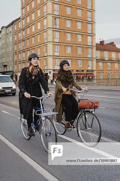 Sweden  Uppland  Stockholm  Vasatan  Sankt Eriksgatan  Man and woman cycling on city street
