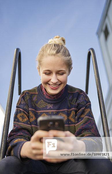 Schweden  Vasterbotten  Umea  Junge Frau am Telefon