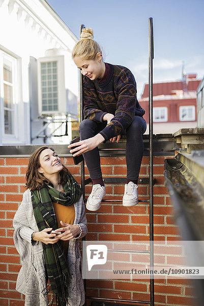 Schweden  Vasterbotten  Umea  Zwei junge Frauen mit Telefonen