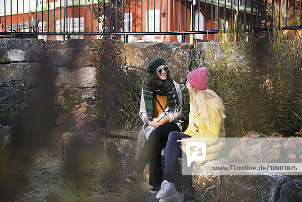 Schweden  Vasterbotten  Umea  Zwei junge Frauen sitzen auf einem Felsvorsprung im Freien